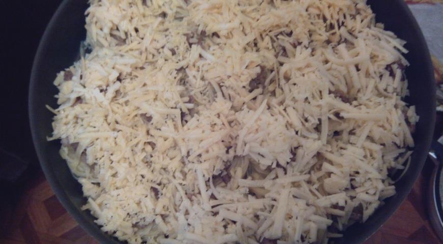 Перед выпеканием посыпаем гнезда сыром