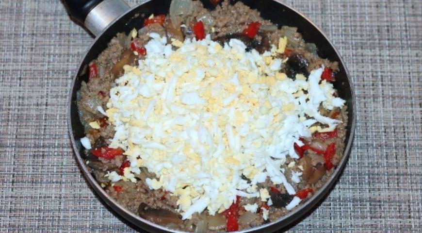 В готовую начинку для пирожков добавляем натертые яйца