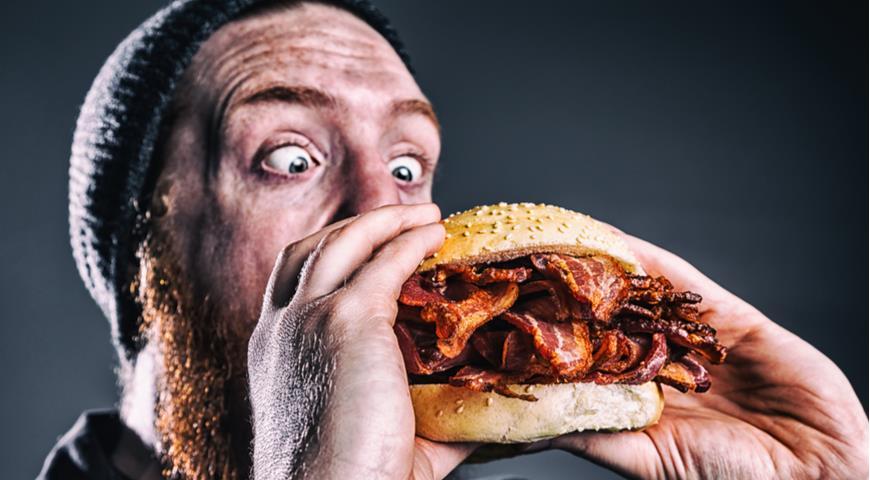 Мужчина ест бургер