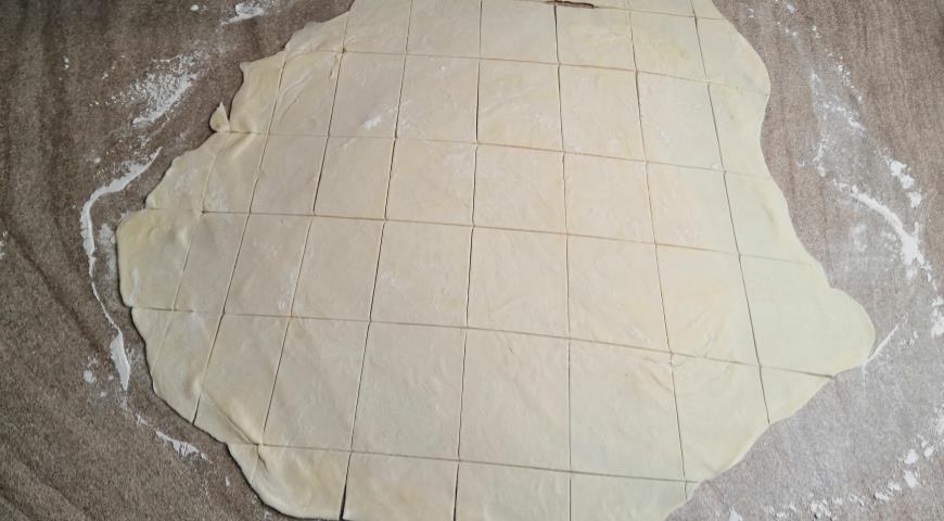Стол посыпаем мукой, катаем тесто до тонкого листа и режем его на кубики