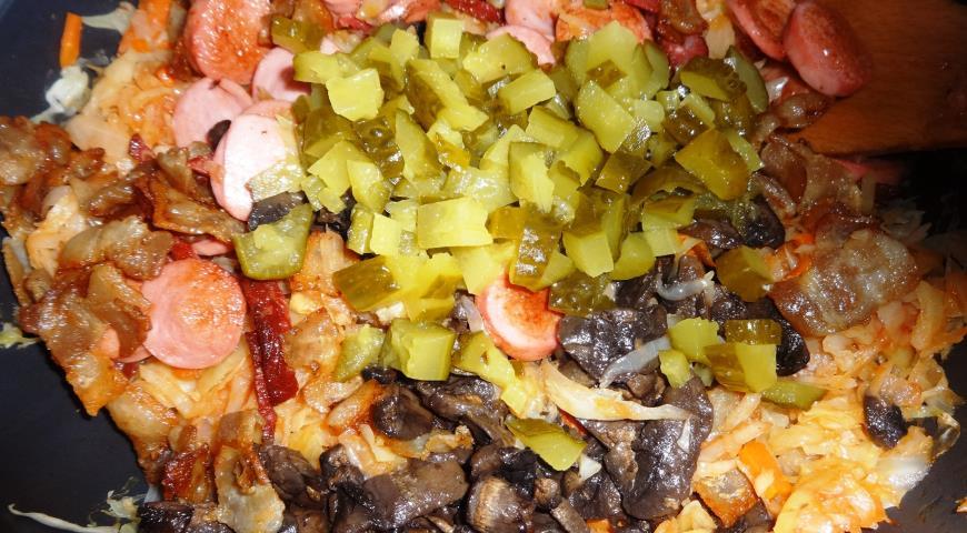 Добавляем огурцы, сосиски, колбасу, бекон и грибы в капусту для солянки