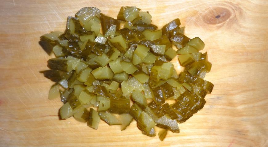Нарезаем соленые огурцы для приготовления солянки с сосисками и беконом