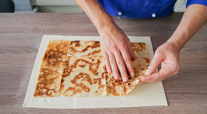 Кулебяка с блинами, капустой, яйцами и грудинкой, выложите блинчики на тесто так, чтобы они закрыли все тесто, кроме кромки