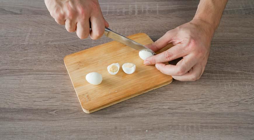 Оливье со свежим огурцом, нарежьте перепелиные яйца половинками