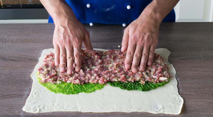 Штрудель с мясом, на пласт теста уложите листья савойской капусты и распределите начинку